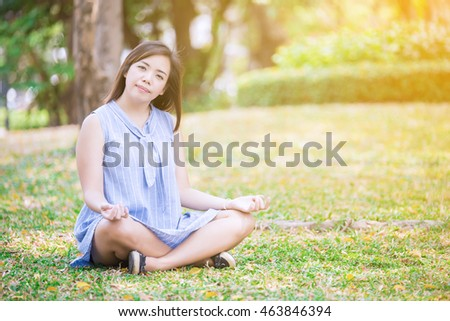 asian girl playing Yoga in the park and looking camera