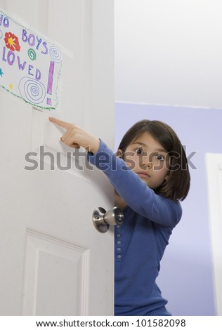 Asian girl pointing at sign on bedroom door - stock photo