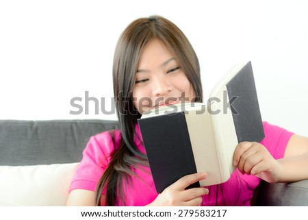 Asian girl reading book with smiling face