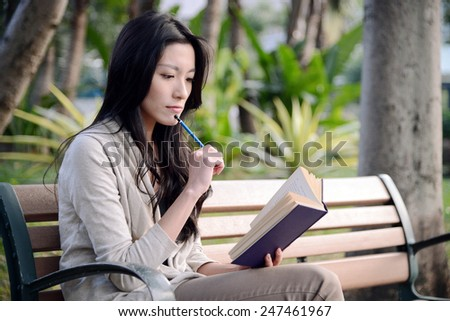 Asian girl reads a book on a wooden bench