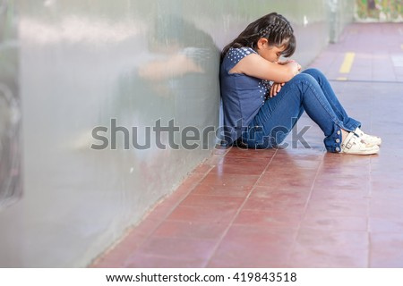Asian girl sad at school. Isolation and bullying concept. - stock photo