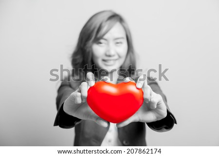 Asian girl show red heart with both hand  focus at the heart on black and white - stock photo