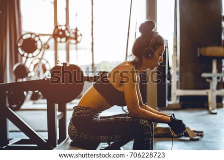 Asian girl sitting and listening to music from mobile phone through headphones. On break time in gym.