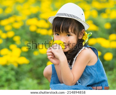 asian girl sitting in a flower meadow - stock photo