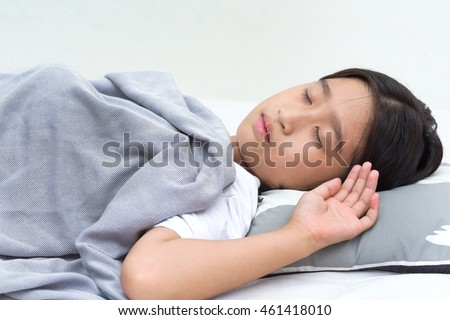 Asian girl sleeping blanket on her bed.