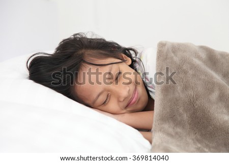 Asian girl sleeping in bed. Nine year old girl a sleep with his head on a pillow and his cheek resting on his hands.
