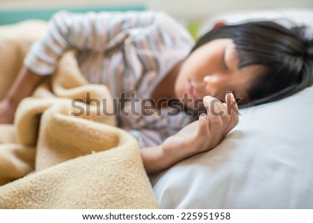 Asian girl sleeping on bed covered with blanket. Selective focused. - stock photo