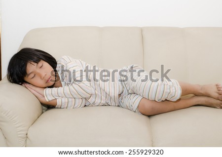 Asian girl sleeping on sofa at home. - stock photo