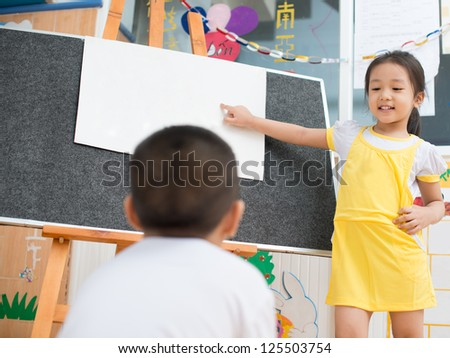 Asian girl standing in front of the board and showing