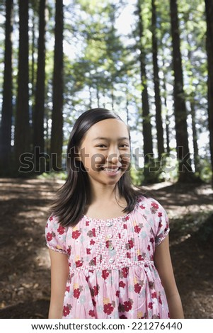Asian girl standing in woods - stock photo