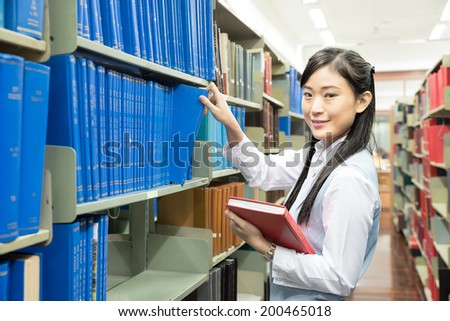 Asian girl student picking a book in a library - stock photo