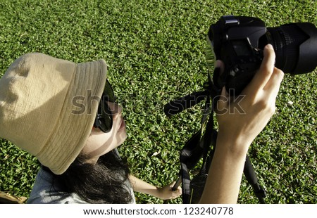 Asian girl taking photos by professional digital camera in park
