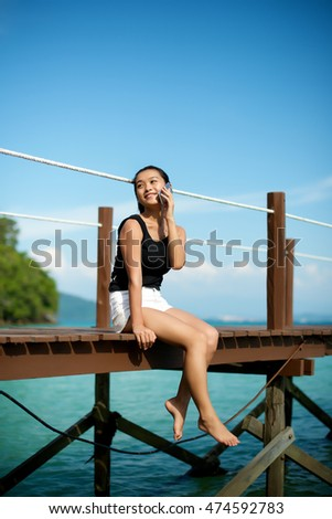 Asian girl talking on the phone at a beach pier
