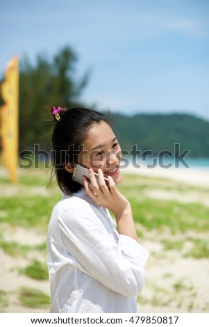 Asian girl talking on the phone at a beach vacation