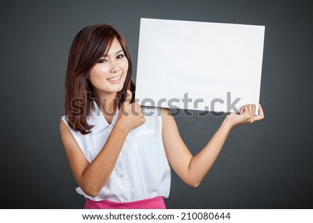 Asian girl thumbs up for  blank sign on gray background
