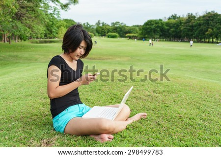 Asian girl type some text on her mobile phone in green garden, young woman sit on green grass