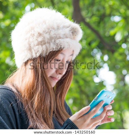 Asian girl using cell phone outdoor - stock photo