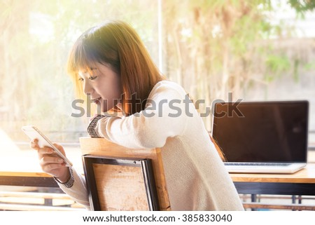 Asian girl using smartphone in cafe or co-working with morning light. - stock photo