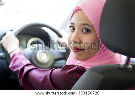 Asian Girl wearing hijab  Driving Happy smiling in a car - stock photo