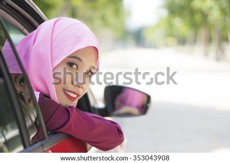 Asian Girl wearing hijab  Driving Happy smiling in a red car - stock photo