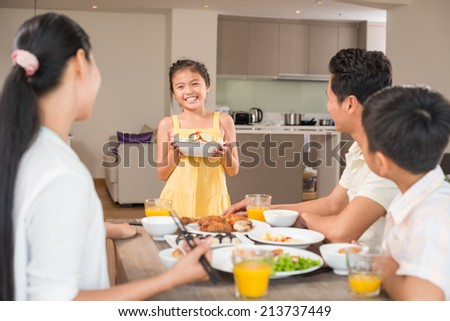 Asian girl with a bowl of salad standing in front of family dinner table
