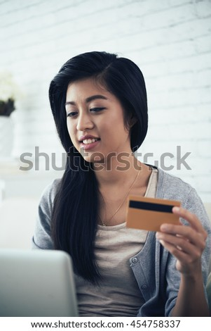 Asian girl with credit card shopping online