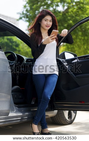 Asian Girl with mobile phone happy smiling in a car - stock photo