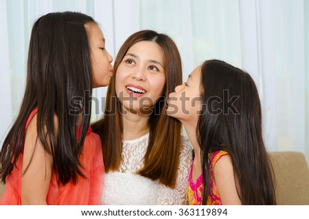 Asian girls kiss their mother - stock photo