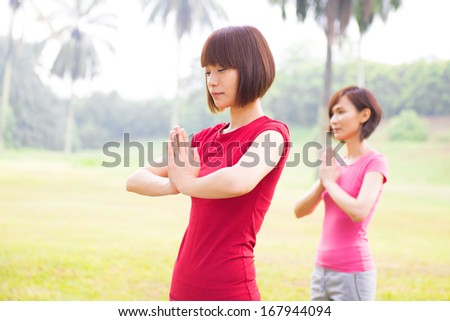 Asian girls performing yoga at outdoor park - stock photo