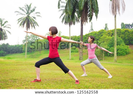 Asian girls practicing yoga outdoor green park - stock photo