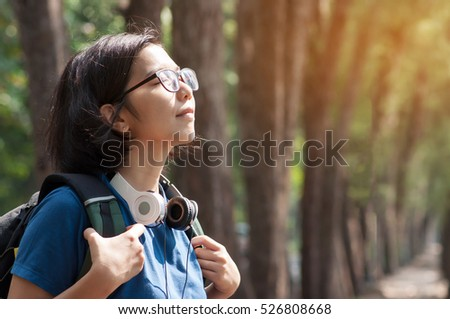 Asian glasses woman hiker with backpack breathing nature fresh air. Beautiful girl with  headphone smiling on nature background.