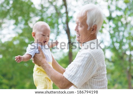 Asian grandfather having fun with his grandson outdoor - stock photo