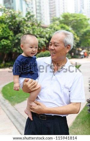 Asian grandfather holding grandson and walking in the garden