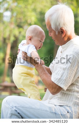 asian grandfather playing with grandkid - stock photo
