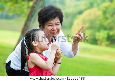 Asian grandmother and granddaughter exploring nature by magnifier - stock photo