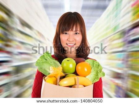 Asian grocery shopping. Smiling young woman holding paper shopping bag full of groceries in a grocery store/supermarket . - stock photo
