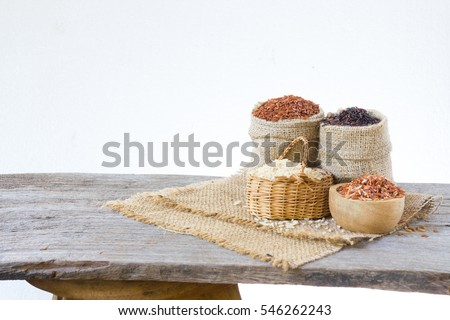 Asian group of grain rice,black rice,red rice ,rice riceberry in gunny bag on old wooden isolate on white background