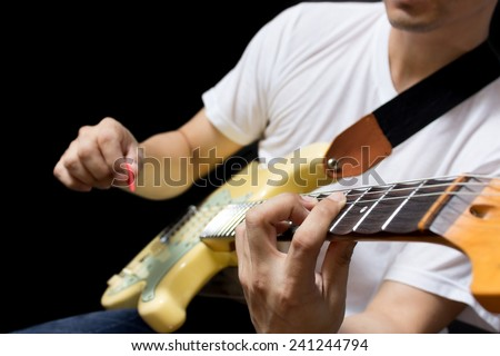 asian guitarist / musician plays electric guitar, isolated on black - stock photo