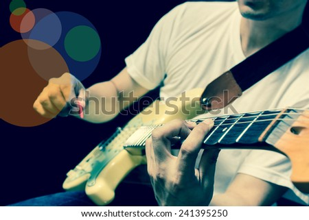 asian guitarist / musician plays electric guitar, isolated on black & cross processed + colorful , beautiful bokeh - stock photo