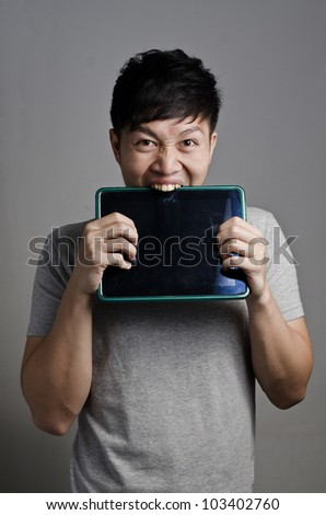 Asian guy bites his tablet