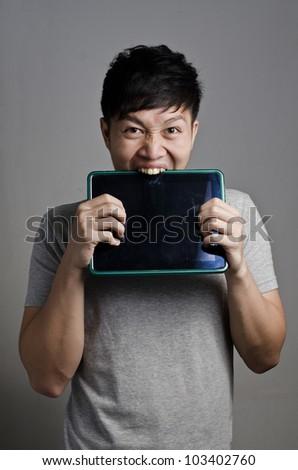 Asian guy bites his tablet - stock photo