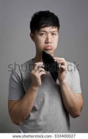 Asian guy look at his empty wallet on gray background