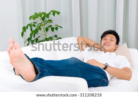 Asian guy resting at home. Asian handsome man relaxed and lying on sofa indoor.