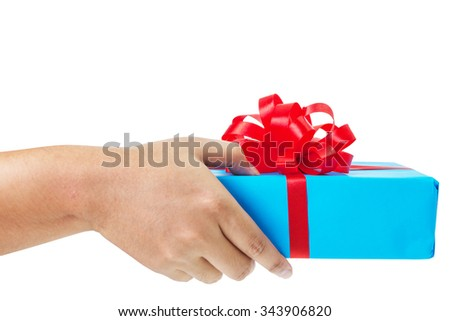 Asian hand giving a gift wrapped in blue box with red ribbon and bow. the most beautiful gift isolated on white background - stock photo