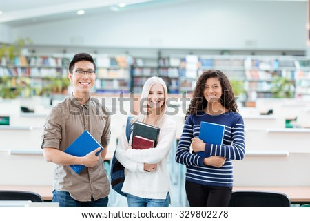 Asian handsome boy in black glasses, blonde girl in white sweater and african american curly woman looking happy - stock photo