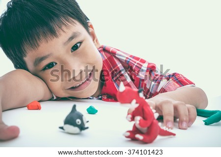 Asian handsome child smiling and show his works from clay, on white background. Strengthen the imagination of child. Vintage picture style. Selective Focus.