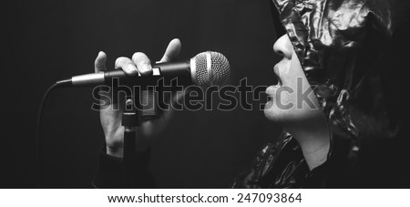 asian handsome male rocker artist in black leather hood jacket singing with dynamic microphone on dark background, bw filter - stock photo