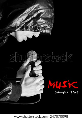 asian handsome male vocal rocker artist in black leather hood jacket singing with dynamic microphone , black and white processed & isolated on black - stock photo