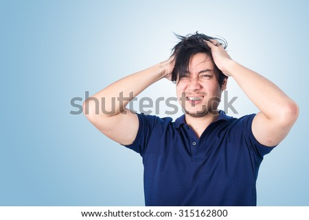 Asian handsome man holding his head frowning with worry screaming. Man pulling his hear for worry, sadness, desperation, so serious, funny, - stock photo