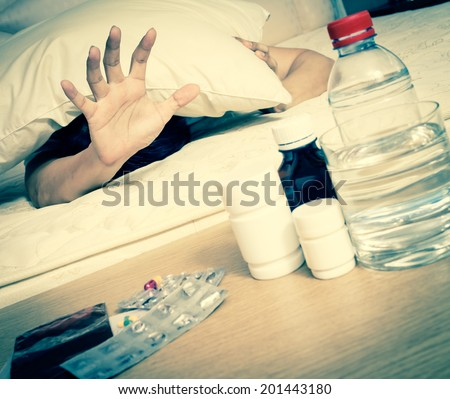 Asian Handsome Man in bed with tablets and water suffering insomnia, hangover and headache - stock photo
